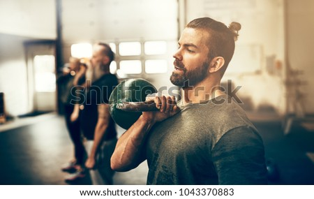 Fit young man in sportswear holding a dumbbell during a workout class in a gym #1043370883