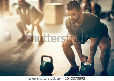 Fit young man in sportswear focused on lifting a dumbbell during an exercise class in a gym #1043370892