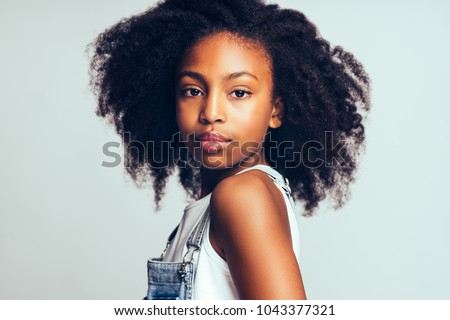 Confident young African girl with long curly hair and wearing dungarees standing alone against a gray background #1043377321