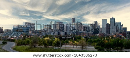 Close up of the Denver skyline with wispy clouds over the city