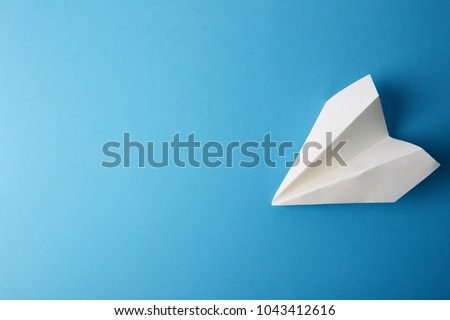 Flat lay of white paper plane and blank paper on pastel blue color background.Horizontal Royalty-Free Stock Photo #1043412616