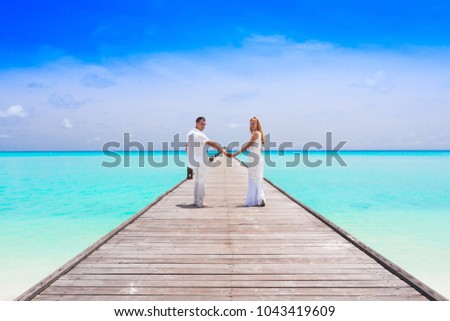 Couple on a tropical beach jetty at Maldives #1043419609