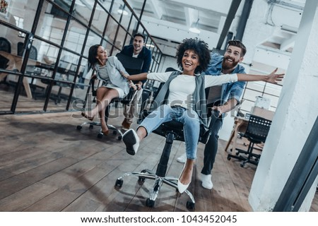 Work hard play hard! Four young cheerful business people in smart casual wear having fun while racing on office chairs and smiling #1043452045
