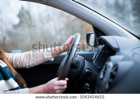 Young woman driving her new car, close-up of hands on a steering wheel #1043454655