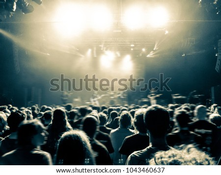 Concert hall with a lit stage and people silhouettes during a concert #1043460637