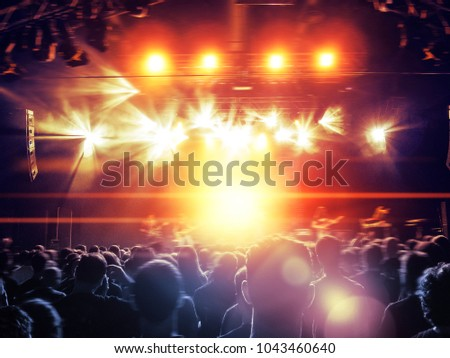 Concert hall with a lit stage and people silhouettes during a concert #1043460640