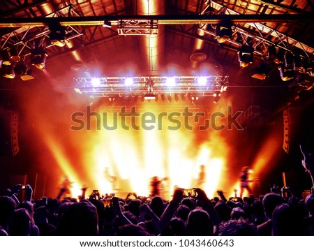 Concert hall with a lit stage and people silhouettes during a concert #1043460643