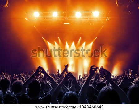 Concert hall with a lit stage and people silhouettes during a concert Royalty-Free Stock Photo #1043460649