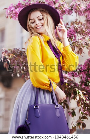 Outdoor portrait of young beautiful happy smiling girl posing in street with blooming trees, wearing stylish hat, yellow shirt, tulle skirt, holding violet handbag. Female spring fashion concept  #1043461456