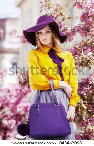 Outdoor portrait of young beautiful girl posing in street with blooming trees, wearing stylish hat, yellow shirt, tulle skirt, holding violet handbag. City lifestyle. Female spring fashion concept  #1043462068