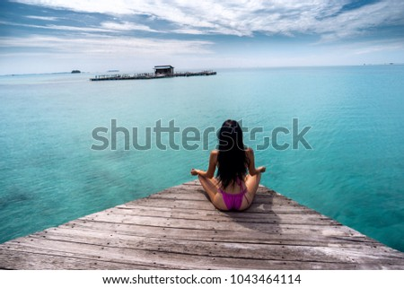 Young woman exercising yoga by the indian ocean Indonesia