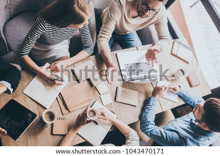 Business meeting. Top view of buiness team brainstorming while sitting at the office table together Royalty-Free Stock Photo #1043470171