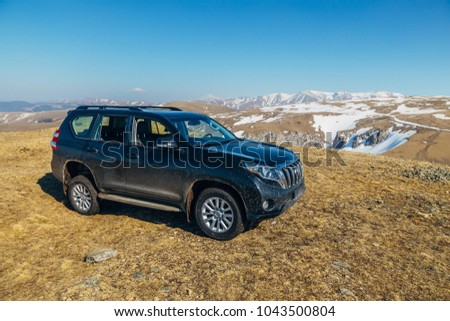Arkhyz, Caucasian mountains, Russia - APRIL 27, 2017:  Black off-road car Toyota Land Cruiser Prado at Caucasian mountains in sunny day #1043500804