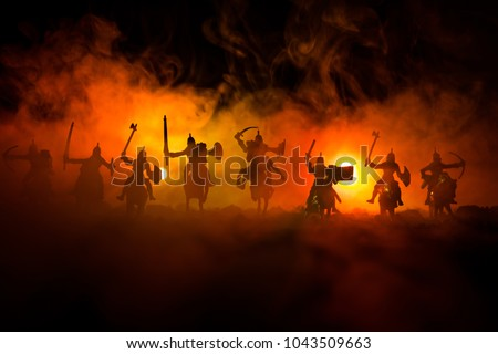 Medieval battle scene with cavalry and infantry. Silhouettes of figures as separate objects, fight between warriors on dark toned foggy background. Night scene. Selective focus Royalty-Free Stock Photo #1043509663
