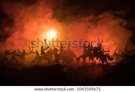 Medieval battle scene with cavalry and infantry. Silhouettes of figures as separate objects, fight between warriors on dark toned foggy background. Night scene. Selective focus #1043509675