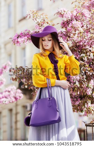 Outdoor portrait of young beautiful girl posing in street with blooming trees, wearing stylish hat, yellow shirt, tulle skirt, holding violet handbag. City lifestyle. Female spring fashion concept  #1043518795