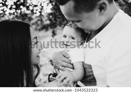 Black and white photo of a beautiful and happy family. Daddy, Mom and their little son, they're all smiling #1043522323