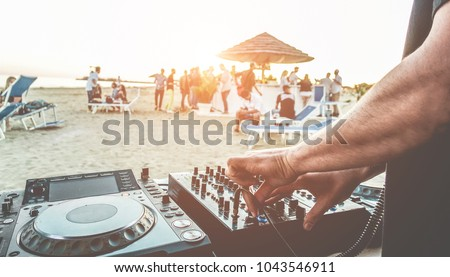 Dj mixing at sunset beach party in summer vacation outdoor - Disc jockey hands playing music for tourist people in chiringuito kiosk bar - Event, music and fun concept - Focus on left hand  #1043546911