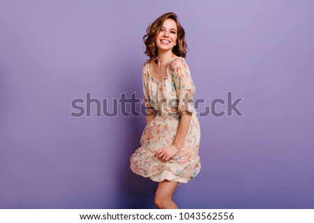 Magnificent girl with light-brown curly hair dancing with smile in purple studio. Indoor portrait of inspired caucasian lady in romantic outfit expressing happy emotions. #1043562556