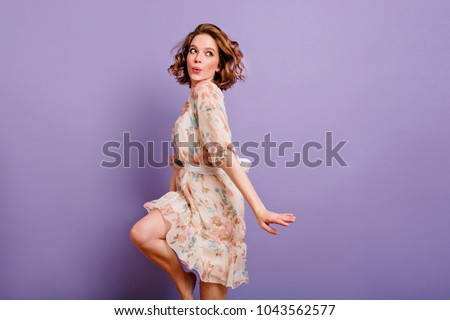 Inspired european young woman dancing in studio and laughing. Winsome brunette girl in cute dress jumping on purple background. #1043562577