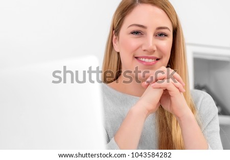 An attractive woman is looking at the camera while sitting at the desk in the workplace or at home. Sitting at the desk with a laptop. Office or work as a freelancer. #1043584282