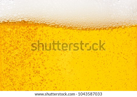 Pouring beer with bubble froth in glass for background on front view wave curve shape texture foam ,  drink alcohol celebration party holiday new year concept #1043587033