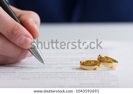 Hands of wife, husband signing decree of divorce, dissolution, canceling marriage, legal separation documents, filing divorce papers or premarital agreement prepared by lawyer. Wedding ring #1043592691