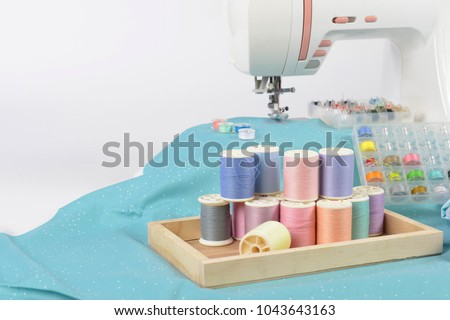 Sewing machine and colorful thread rolls, scissors, fabric and accessories for sewing on white background, Sewing and needlework concept. (Selective Focus) #1043643163