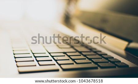 Photo of a laptop keyboard with selective focus on the keys and a soft and warm bokeh background.  #1043678518