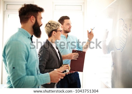 Creative business team working on project. Creative director is showing chart to the workers. #1043751304