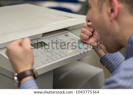 angry young business man beats his fist on a multifunction printer or copier #1043775364