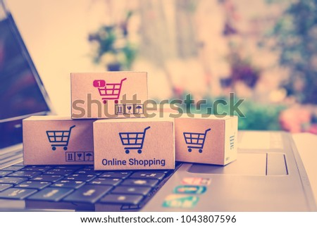 Online shopping / ecommerce and delivery service concept : Paper boxes with shopping cart logo on a laptop keyboard, depicts trendy customers always order things from retailer sites over the internet. #1043807596