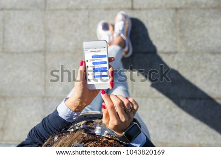 Woman using instant messaging app on mobile phone Royalty-Free Stock Photo #1043820169