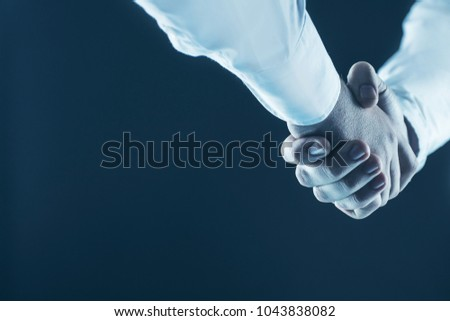 concept of a reliable partnership: a close-up of handshake of business partners on a black background. #1043838082