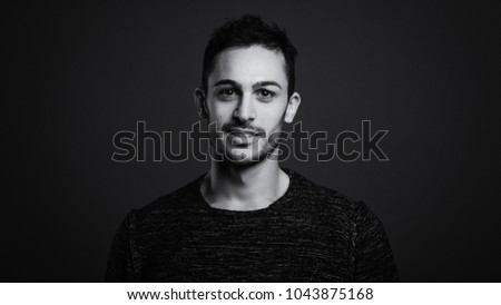 Smiling man close up portrait against dark grey background. Black and white image.