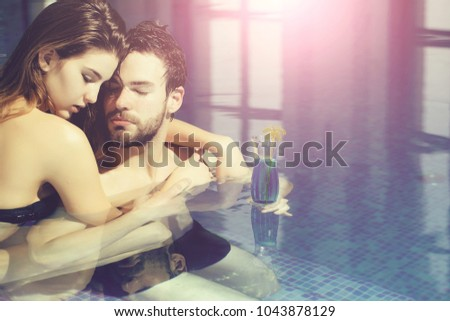 wet couple of pretty woman or sexy girl and handsome bearded man or guy with muscular body in swimming pool with blue water holds cocktail glass, copy space #1043878129