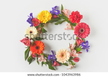 top view of floral wreath made of beautiful colorful flowers and green leaves on grey #1043963986