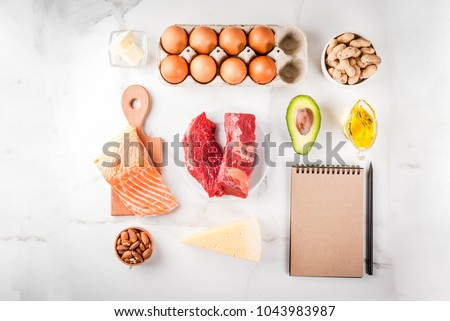 Ketogenic low carbs diet concept. Healthy balanced food with high content of healthy fats. Diet for the heart and blood vessels. Organic ingredients, white background, copy space top view, notepad  #1043983987