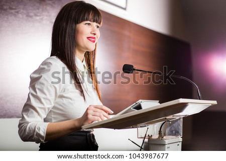 Pretty, young business woman giving a presentation in a conference/meeting setting (shallow DOF; color toned image) #1043987677