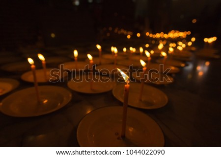 Candles in the dark blur background,Close Up light candle flame,yellow burning candle on dark tone background #1044022090