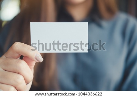 A business woman holding and showing empty business card in office