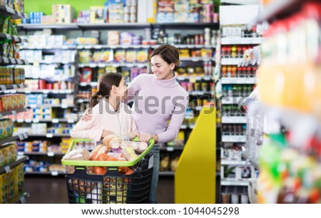 Attractive woman with teenage daughter restocking for family in supermarket #1044045298
