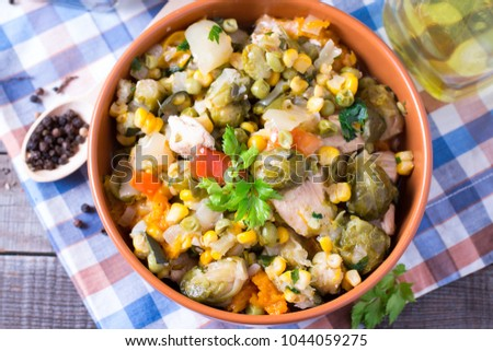 Vegetable stew. Stewed vegetables in in a plate on an old wooden table. Selective focus. #1044059275