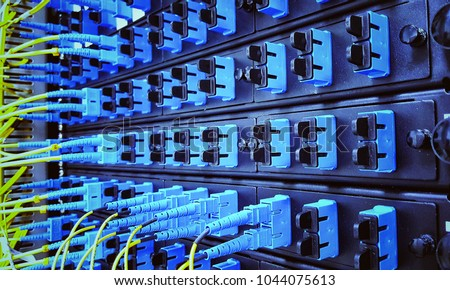 Close up fiber optic in server room , network cables installed in the rack  #1044075613