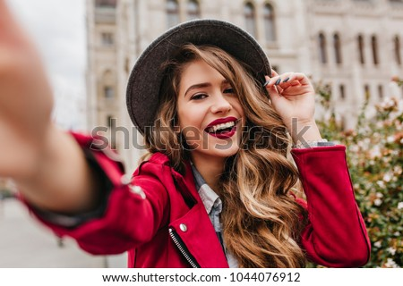 Portrait of wonderful white female model with bright makeup expressing energy in good day in Europe. Lovely curly woman in stylish hat making selfie while walking past old building. #1044076912