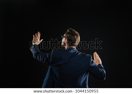 Correct the mistake. Busy responsible smart man standing in the dark room holding hands up and working with the invisible touchscreen. #1044150955