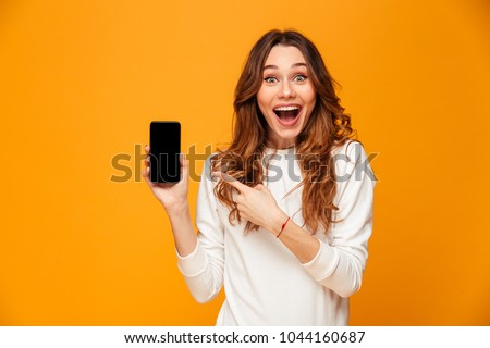 Surprised happy brunette woman in sweater showing blank smartphone screen and pointing on it while looking at the camera with open mouth over yellow background Royalty-Free Stock Photo #1044160687