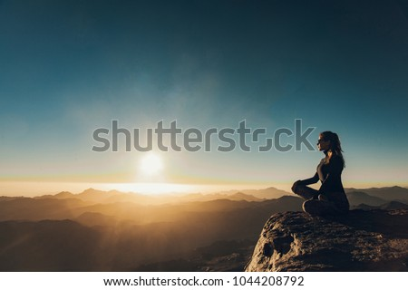 Woman sits in a pose of yoga on edge of cliff on Mount Sinai and meditates against background of beautiful sunrise in Egypt. #1044208792