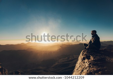 Man sits in a pose of yoga on edge of cliff on Mount Sinai and meditates against background of beautiful sunrise in Egypt. #1044212209