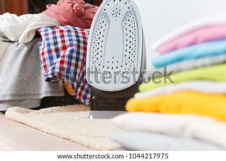 Close up steam iron, ironing colorful clothes, washed laundry, family clothing on ironing board isolated on white background. Housekeeping concept. Copy space for advertisement. With place for text #1044217975